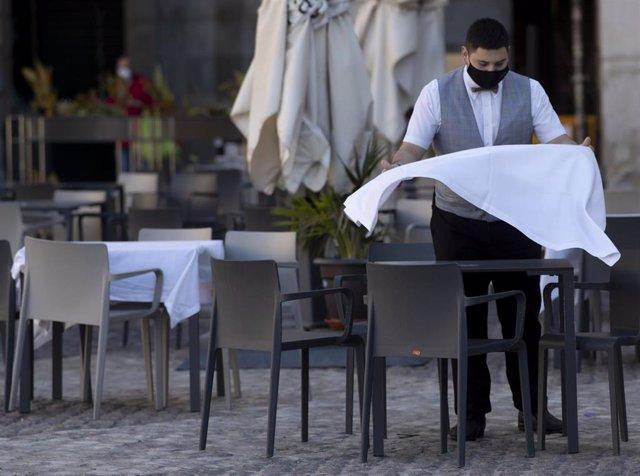 Un camarero prepara la mesa de una terraza de un establecimiento