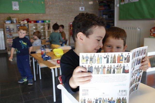 Primer pla d'uns nens mirant un llibre de gegants a l'escola Cor de Roure de Santa Coloma de Queralt (Conca de Barberà). Imatge publicada el 19 d'octubre del 2020. (Horitzontal)