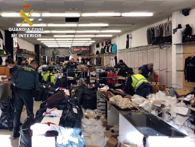 Agents de la Guàrdia CIvil durant la inspecció a la botiga d'Els Límits on van intervenir 5.100 articles falsificats. Imatge cedida aquest 20 d'octubre del 2020 (Horitzontal)
