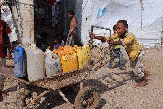 Un niño transporta una carretilla con bidones en Adén