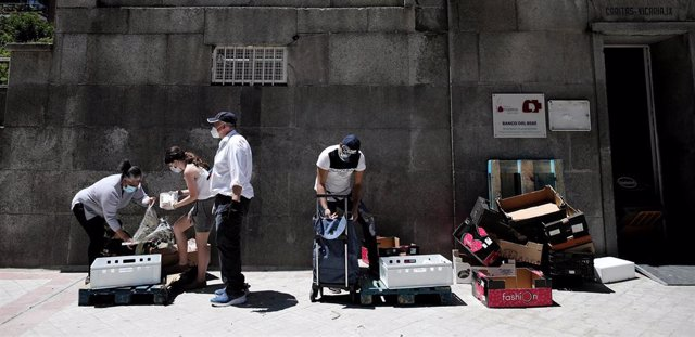 Varias personas recogen alimentos que les dan dos voluntarios a las puertas de la Parroquia Santa María Micaela. En Madrid (España), a 29 de mayo de 2020.