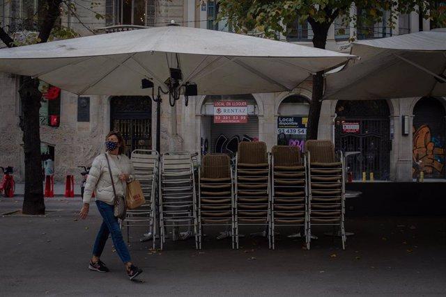 Una mujer pasa junto a la terraza recogida de un bar cerrado durante el cuarto día de la entrada en vigor de las nuevas restricciones en Cataluña, en Barcelona, Cataluña (España) a 20 de octubre de 2020.