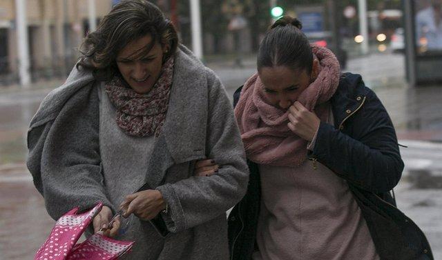 Dos mujeres se protegen del viento