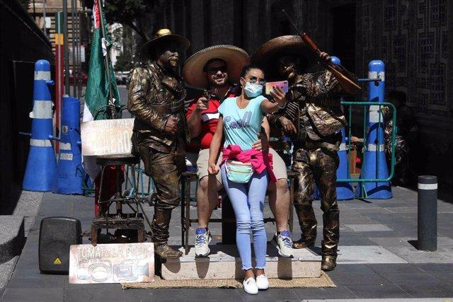 Un grupo de turistas se fotografían junto a unas estatuas situadas en el centro histórico de Ciudad de México.