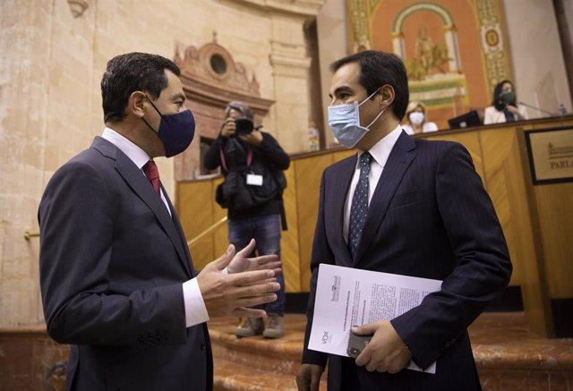 El presidente de la Junta de Andalucía, Juanma Moreno (i), junto al portavoz del grupo parlamentario popular, José Antonio Nieto, al inicio de la segunda jornada del Debate sobre el Estado de la Comunidad en el Parlamento de Andalucía