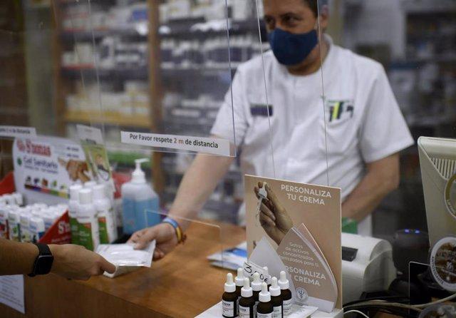 Un farmacéutico entrega a un cliente una de las mascarillas KN95 que ha recibido en su farmacia, en Madrid (España), a 30 de septiembre.