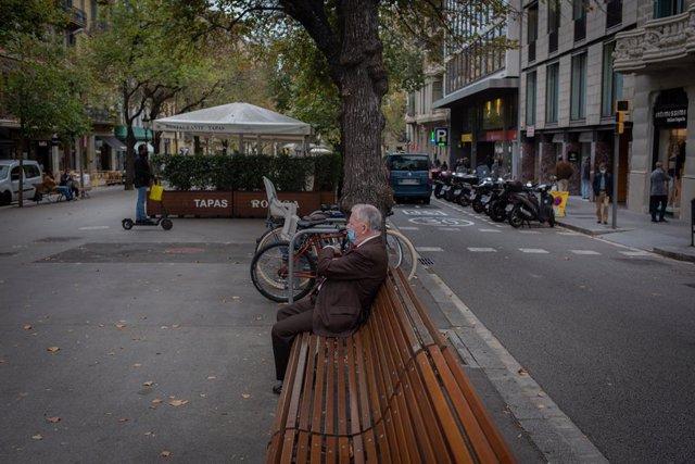 Un home descansa en un banc. Barcelona, Catalunya (Espanya), 20 d'octubre del 2020.