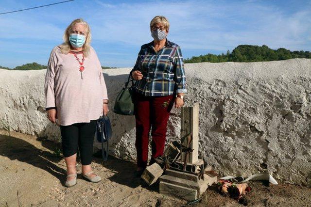 Pla sencer de Lígia Cabot (esquerra) i Laura Niubó al costat d'una creu dedicada als seus tiets -soldats republicans durant la Guerra Civil- a la fossa del cementiri de Salomó on es creu que estan enterrats. Imatge del 21 d'octubre del 2020. (Horitzontal)