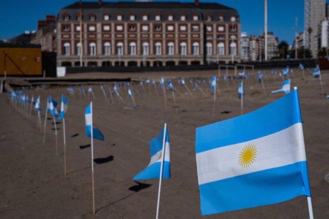 Banderas argentinas sobresalen de la arena de una playa en memoria de las víctimas del coronavirus, en la ciudad costera de Mar del Plata.