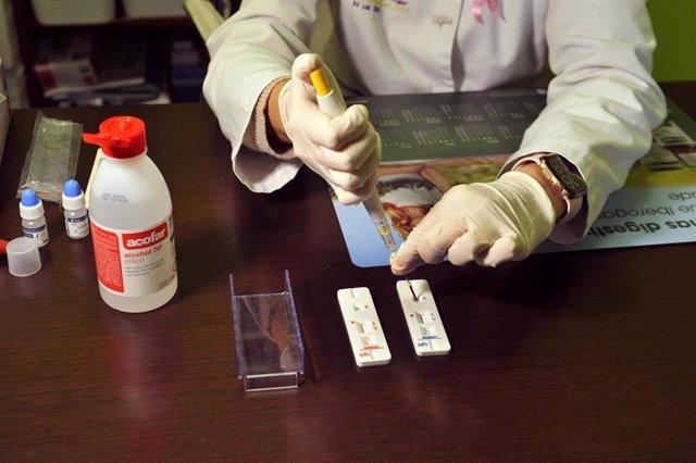 Una farmacéutica de la Farmacia Portal Martínez Soto introduce en una placa la muestra de sangre que ha tomado para realizar un test de cribado del coronavirus en Barbadás.