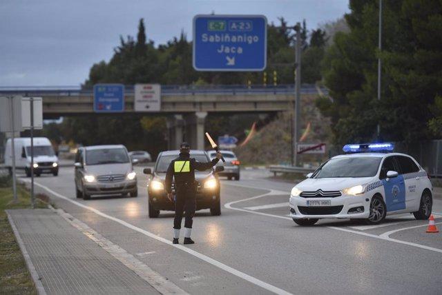 Un agente de la Policía de Huesca realiza controles de entradas y salidas a la ciudad, en la calle Doctor Artero, en Huesca.