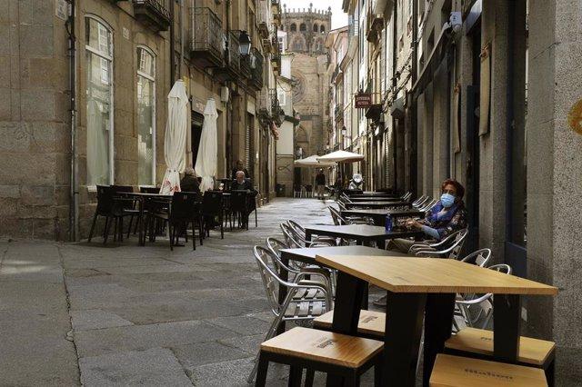Una mujer permanece sentada en una terraza del barrio de O Couto en Ourense.