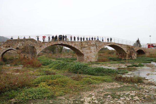 Pla general d'alcaldes, cossos de seguretat i voluntaris dalt del pont Vell de Montblanc, assistents en un acte commemoratiu per l'aniversari de la riuada a la Conca. Imatge del 22 d'octubre del 2020. (Horitzontal)