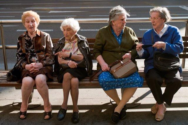 Cuatro mujeres mayores sentadas en un banco.