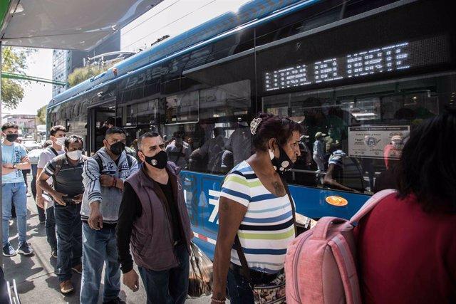 Un grupo de personas espera su turno para tomar el autobús en Ciudad de México.