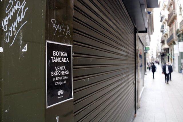El cartell d'un comerç tancat a l'Eix Comercial de Lleida en primer pla i el carrer amb gent de fons. Imatge del 20 d'octubre de 2020. (Horitzontal)