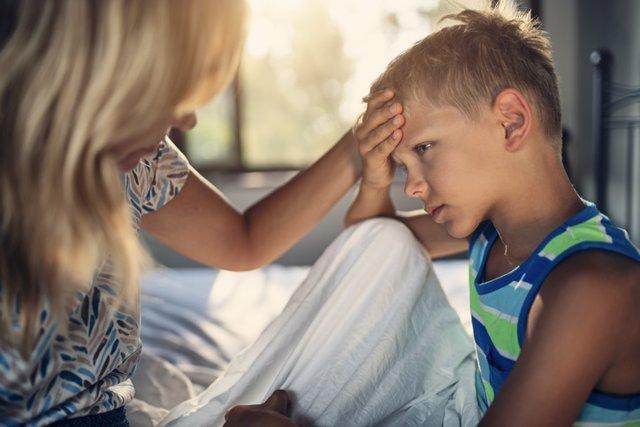 Madre mirando si su hijo tiene fiebre o dolor de cabeza.