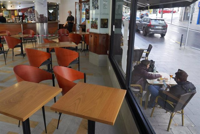 Dos personas toman el aperitivo en una mesa de la terraza de un bar, en Santiago de Compostela, A Coruña (Galicia)