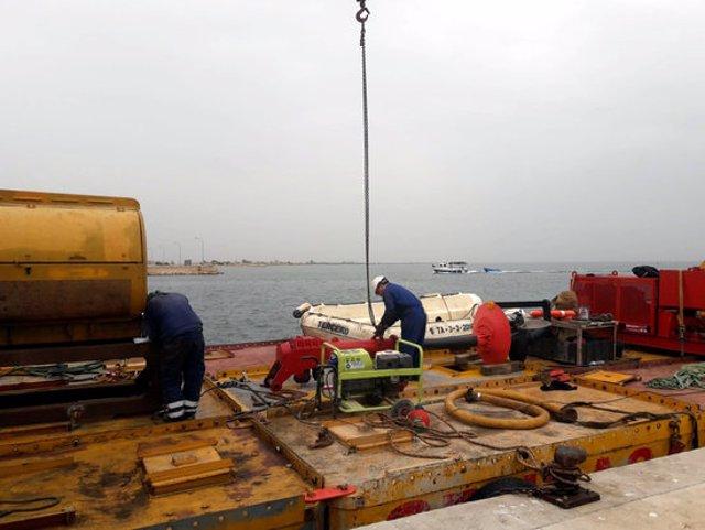 Pla general de tècnics de Costes muntant la pontona que servirà per al desmantellament del 'Xiringuito' dels Alfacs, al port de la Ràpita. Imatge del 23 d'octubre del 2020 (horitzontal)