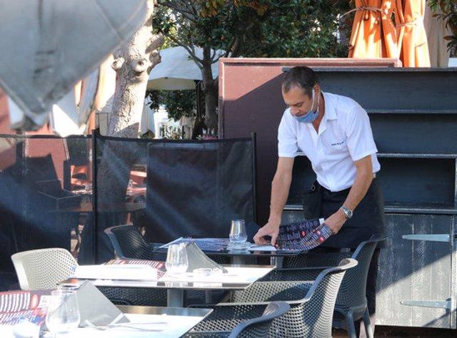 Un cambrer preparant taules en un restaurant de Perpinyà aquest 23 d'octubre del 2020. (Horitzontal)