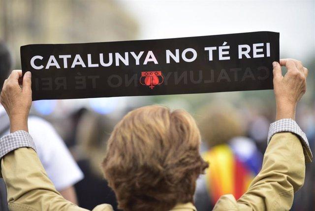 """Una mujer sostiene una pancarta donde se puede leer """"Cataluña no tiene Rey"""" en la cadena humana formada como signo de protesta por la visita del Rey a Barcelona, Catalunya, (España), a 9 de octubre de 2020."""