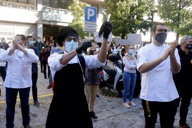 Un cuiner protestant amb una espàtula i una tapa d'olla durant la concentració de l'hostaleria gironina aquest 23 d'octubre del 2020 (Horitzontal)