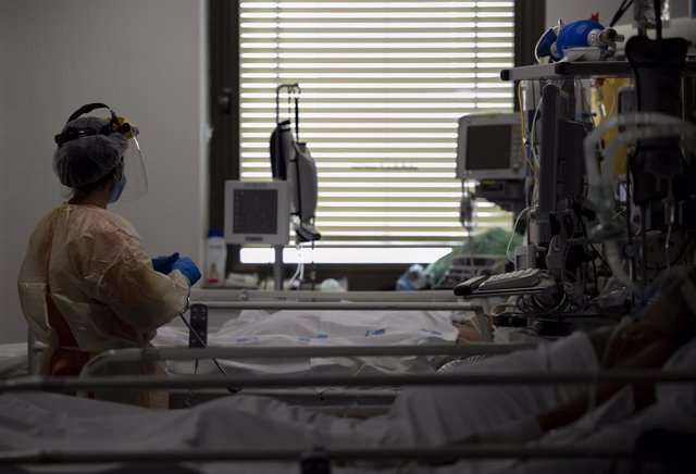 Un sanitari atén un pacient a l'UCI (Arxiu)