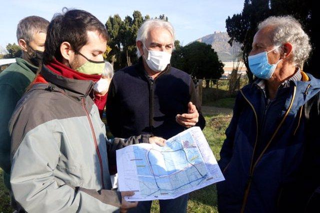 El representants de les entitats naturalistes i el d'Unió de Pagesos, mirant el plànol de les dues alternatives que es proposen per a la variant de Torroella aquest 19 d'octubre del 2020 (Horitzontal)