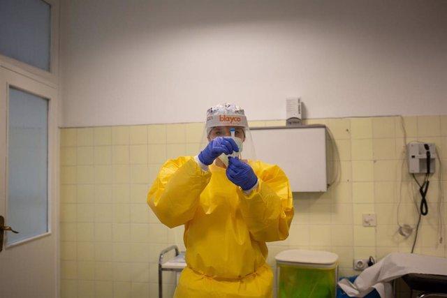 Una sanitaria sostiene uno de los test rápidos de antígenos de detección de coronavirus .