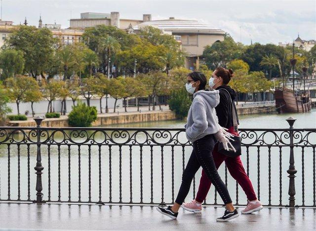 Dos jovenes con mascarillas paseando andando por el puente de Triana en el tercer día de alarma. Sevilla a 17 de marzo 2020