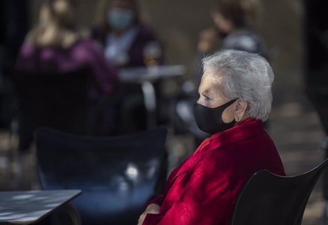 Una mujer mayor con mascarilla en la terraza de un bar. En Sevilla (Andalucía, España), a 23 octubre de 2020.