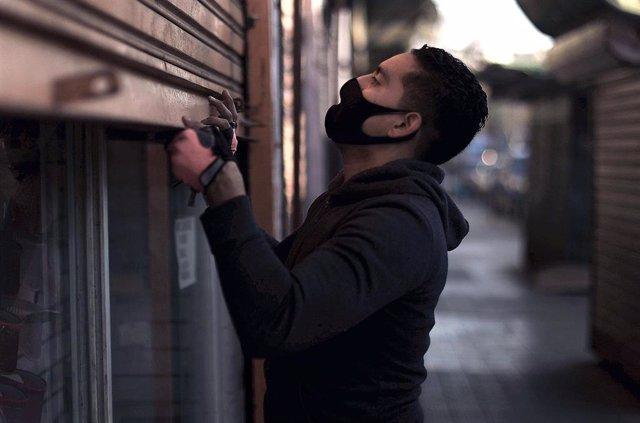 Un hombre reabre su tienda en Santiago de Chile durante la pandemia.