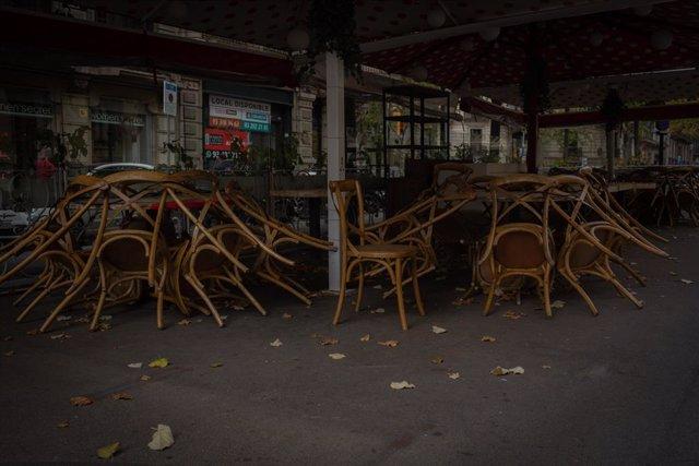 Cadires recollides d'una terrassa d'un bar tancat durant el quart dia de l'entrada en vigor de les noves restriccions a Catalunya, a Barcelona, Catalunya (Espanya) a 20 d'octubre de 2020. Arxiu.