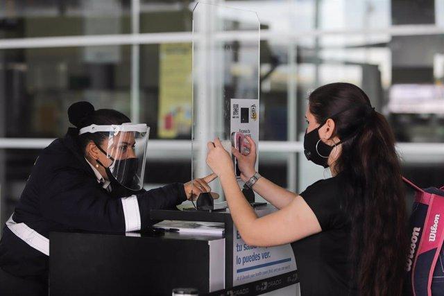 Una mujer es atendida por otra en un mostrador en el aeropuerto de Bogotá