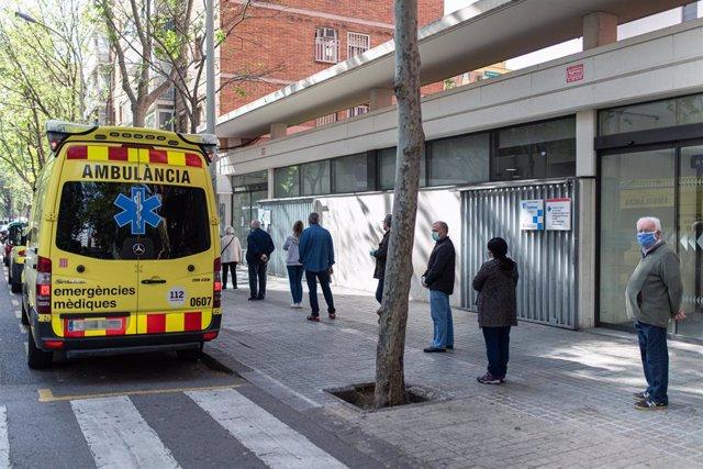 Diverses persones fan cua respectant la distància de seguretat per entrar en un ambulatori al costat de l'Ambulància de Sistema d'Emergències Mèdiques (SEM) de la Generalitat de Catalunya, a Barcelona/Catalunya (Espanya) el 19 d'abril del 2020.