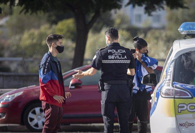 Un agente de la policía local para a un joven por no llevar mascarilla.