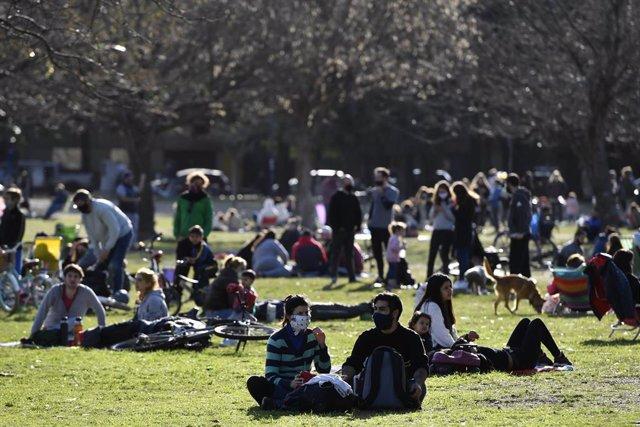Personas sentadas en un parque de Buenos Aires
