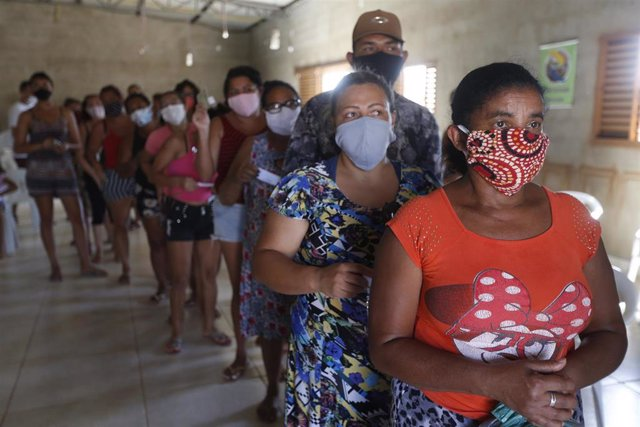 Un grupo de personas residentes de uno de los suburbios de Brasil esperan para recibir alimentos y material sanitario, en medio de la criris del coronavirus.
