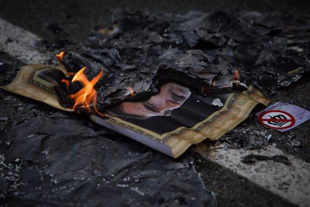 Manifestants independentistes cremen fotografies de Felipe VI i del president del Govern central, Pedro Sánchez, durant la concentració de protesta per la seva presència a Barcelona, Catalunya.