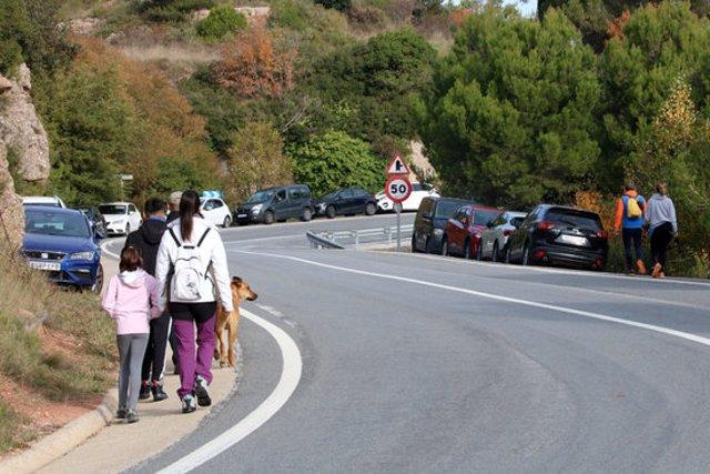 Gran pla general de la carretera d'accés a Montserrat des del Bruc, amb el voral ple de cotxes i excursionistes caminant. Imatge del 25 d'octubre del 2020 (horitzontal)
