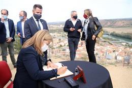 Pla mitjà de la consellera de Cultura, Àngels Ponsa, signant el llibre d'honor d'Ascó des del castell. Foto del 25 d'octubre del 2020 (vertical).