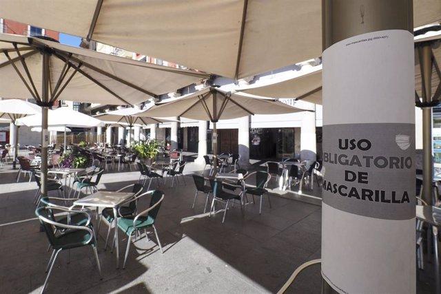 Cartel en el que se lee 'Uso obligatorio de mascarilla' junto a una terraza de un bar en la Plaza Mayor de Valladolid.  .
