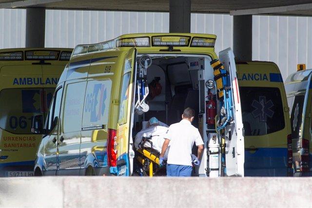 Un profesional sanitario baja de una ambulancia en camilla a un paciente con Covid-19