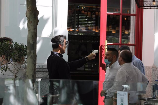 Un camarero mide la temperatura de sus clientes en una céntrica terraza madrileña en el primer día de la Fase 1, cuando se reabren al público las terrazas al aire libre de los establecimientos de hostelería y restauración limitándose al 50% de las mesas y