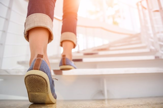 874231466 Young adult woman walking up the stairs with sun sport background.