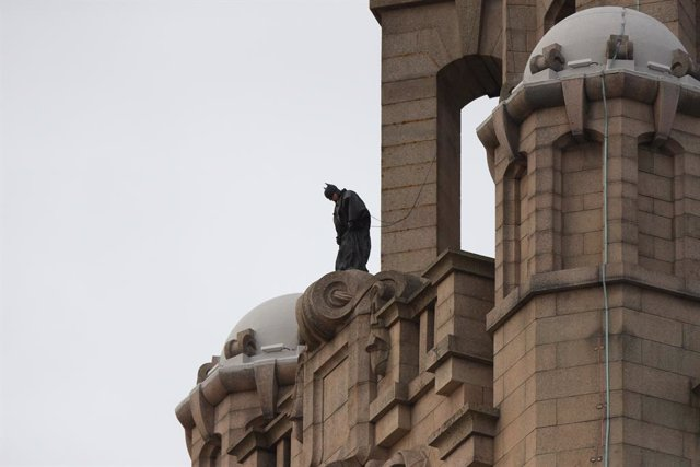 15 October 2020, England, Liverpool: A stuntman secured by a safety wire, stands on top of The Royal Liver Building in Liverpool during filming of The Batman. Photo: Peter Byrne/PA Wire/dpa