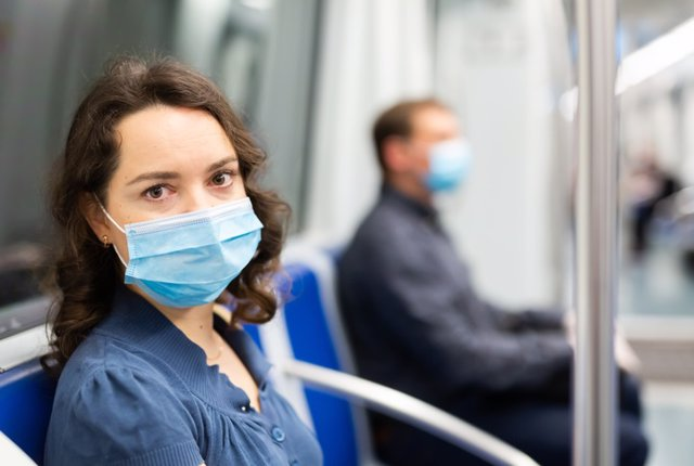 Brunette in medical mask in subway car  Young brunette in medical face mask and protective gloves riding in modern subway car. Concept of forced city trip in context of coronavirus pandemic