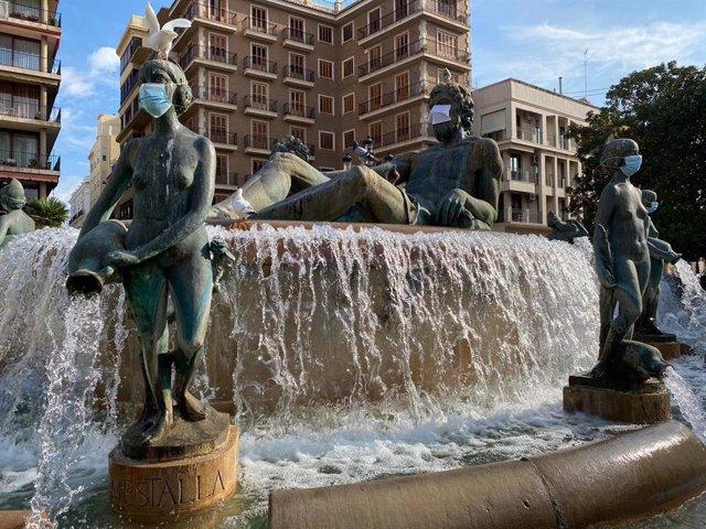 Esculturas de la fuente de la Plaza de la Virgen de València con mascarillas para concienciar a la ciudadanía sobre la necesidad de su uso frente de la Covid-19.