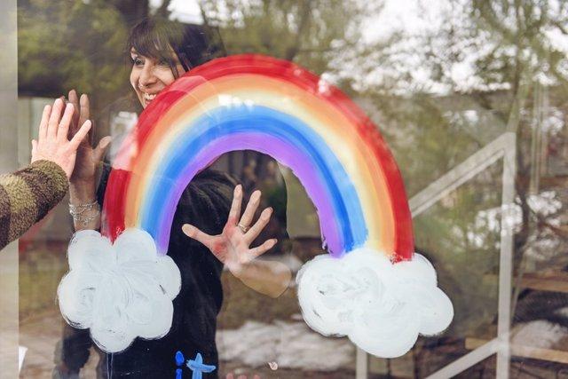 Mujer pintando un arco iris en una ventana.