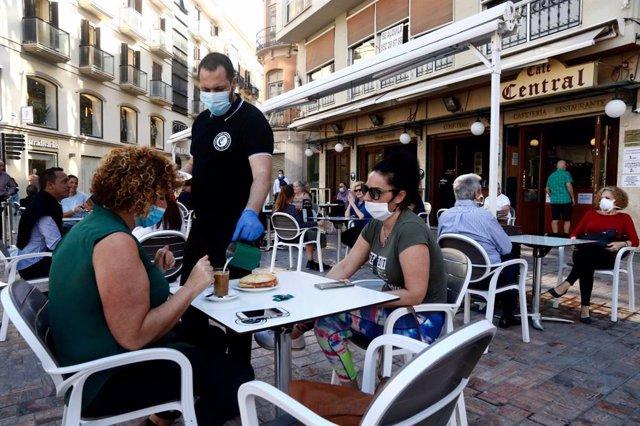 Imagen de archivo de un camarero atendiendo una terraza en Málaga.